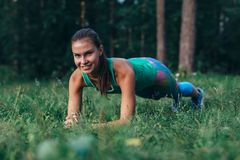 Pretty sporty young female athlete doing planking exercise smiling, looking at camera, working out outdoors royalty free stock images