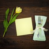 Pretty Spring Table Place Setting with Yellow Tulip, silverware, cloth napkin and a blank green menu card with room or space for c