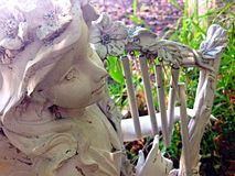 Pretty statue. A statue holding a harp, wind chimes to cheer up the garden Royalty Free Stock Photography