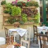 Pretty street side restaurant with little tables and lush plants stock photo