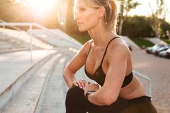 Pretty strong young sports woman make sports stretching exercises. Image of pretty strong young sports woman standing outdoors make sports stretching exercises Stock Image