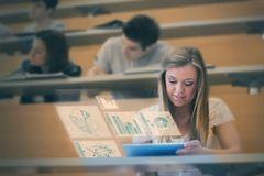 Pretty student analysing graphs on her digital tablet. In lecture hall Stock Photos
