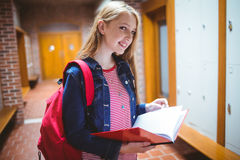 Pretty student with backpack holding notebook looking at the camera Stock Photo