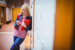 Pretty student with backpack leaning against the locker Stock Photography
