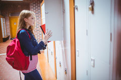 Pretty student with backpack putting notebook in the locker Royalty Free Stock Images
