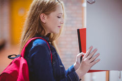 Pretty student with backpack putting notebook in the locker Stock Image