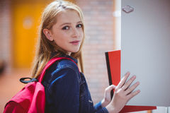 Pretty student with backpack putting notebook in the locker Stock Photography