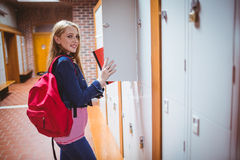 Pretty student with backpack putting notebook in the locker Royalty Free Stock Photos