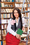 Pretty student with book in library Stock Photos