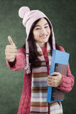 Pretty student with book showing thumbs-up Royalty Free Stock Photography