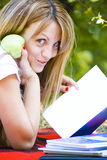 Pretty student with books and apple. Beautiful young woman with books and apple outdoors Royalty Free Stock Photo