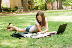 Pretty student doing homework. A pretty young college or high school age girl with study materials stock image