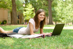 Pretty student doing homework. A pretty young college or high school age girl with study materials stock photography