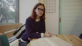 Pretty student girl in glasses studying at table with books stock footage