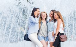 Pretty student girls having fun outdoors. A group of attractive cheerful women talking near the fountain in the city. stock photography