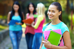 Pretty student with group of people on background Royalty Free Stock Photography