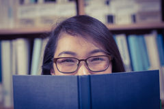 Pretty student hiding face behind a book Royalty Free Stock Images