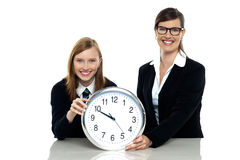 Pretty student holding clock with her teacher Stock Photography