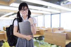 Pretty student holding laptop in class Stock Image
