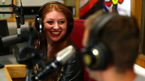 Pretty student interviewing someone for radio in the studio