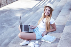 Pretty Student with Laptop Sitting on the Stairs Royalty Free Stock Images