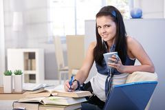Pretty student learning at home smiling Stock Photo