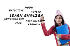 Pretty student learns English. Young asian student in winter clothes learns English and write English material on whiteboard Stock Image