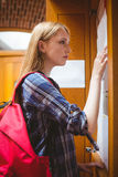 Pretty student looking at notice-board Royalty Free Stock Photography