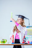Pretty student looks at reagent in test tube royalty free stock photography