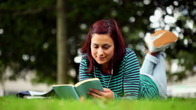 Pretty student lying on grass reading a book listening to music stock video footage