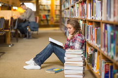 Pretty student reading book on library floor Royalty Free Stock Photo