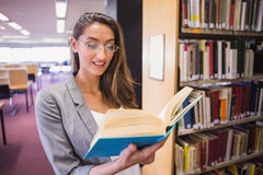 Pretty student reading book in library Stock Images