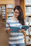 Pretty student reading a book in library Stock Photo