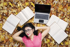 Pretty student relaxing on autumn leaves Royalty Free Stock Images