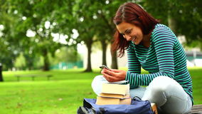 Pretty student sending a text on the grass. At the university stock video footage