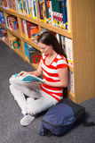 Pretty student sitting on floor reading book in library Royalty Free Stock Photo