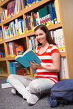 Pretty student sitting on floor reading book in library Stock Photos