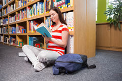 Pretty student sitting on floor reading book in library Royalty Free Stock Photography