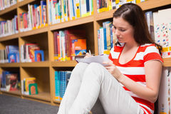 Pretty student sitting on floor reading book in library Stock Images