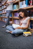 Pretty student sitting on floor reading book in library Royalty Free Stock Images