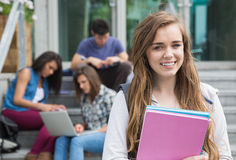 Pretty student smiling at camera outside. At the university Stock Images
