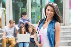 Pretty student smiling at camera outside. At the university Royalty Free Stock Image