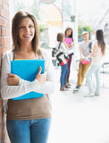 Pretty student smiling and holding notepads Royalty Free Stock Photos