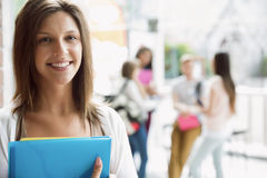 Pretty student smiling and holding notepads Royalty Free Stock Photography