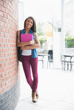 Pretty student smiling and holding notepads Stock Photography