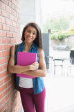 Pretty student smiling and holding notepads Royalty Free Stock Photo