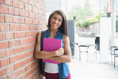 Pretty student smiling and holding notepads Stock Photo