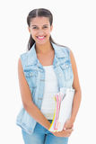 Pretty student smiling and holding notepads Royalty Free Stock Image
