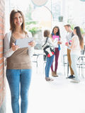 Pretty student smiling and holding tablet Royalty Free Stock Photography