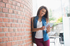 Pretty student smiling and holding tablet Stock Image